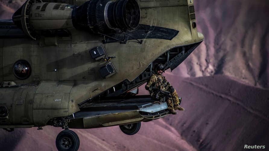 جندي أميركي يجلس في مروحية عسكرية خلال تحليقها في أفغانستان عام 2018