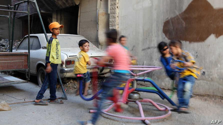 أطفال يلعبون في إحدى مناطق الغوطة الشرقية بعد دخول الهدنة حيز التنفيذ