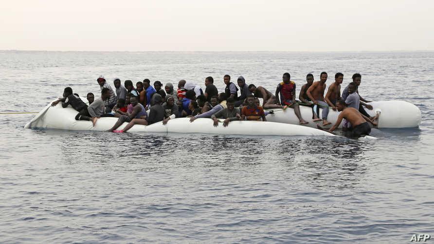 مهاجرون أفارقة ينتظرون إنقاذهم بعد غرق قاربهم المطاطي قبالة سواحل ليبيا- أرشيف