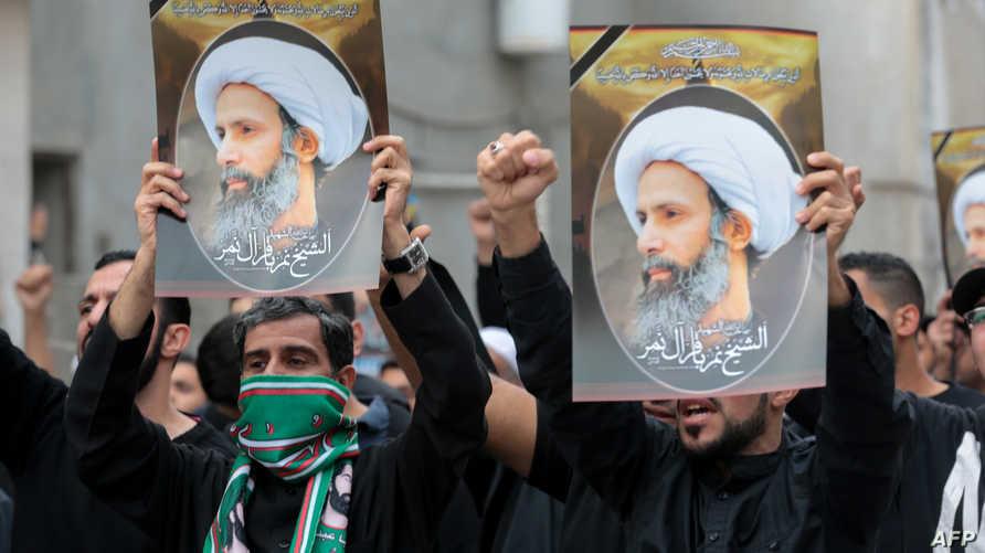 سعوديون شيعة يحملون صور الشيخ نمر النمر خلال تظاهرة في القطيف الجمعة
