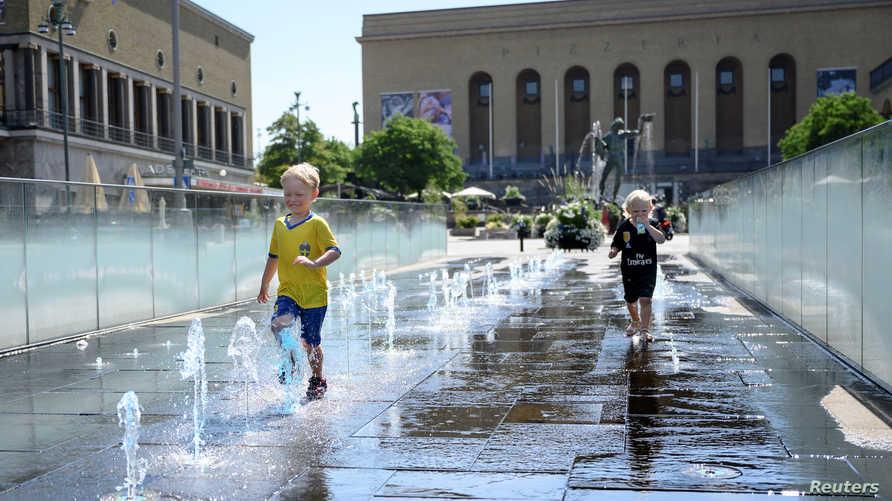طفلان يلعبان في نافورة في غوتابلاستن في السويد  التي وصلتها موجة الحر