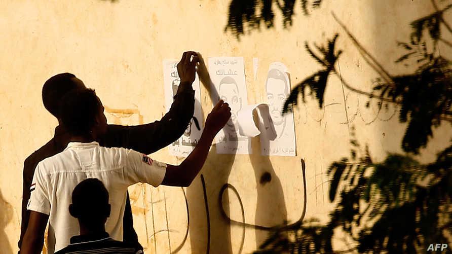 مناصران للبشير يحاولان إزالة شعارات معارضة عن أحد الجدران في الخرطوم