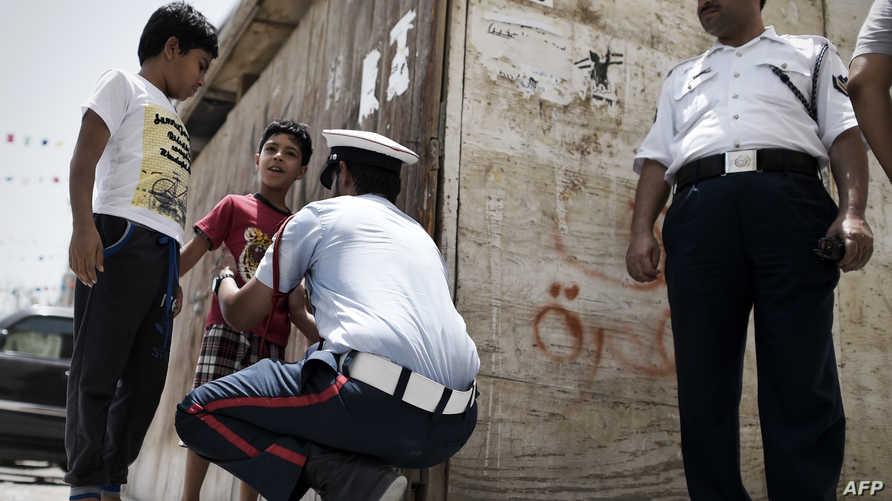 عنصران من الشرطة البحرينية أحدهما يفتش طفلا قرب مسجد في قرية راس الرمان الشيعية -أرشيف