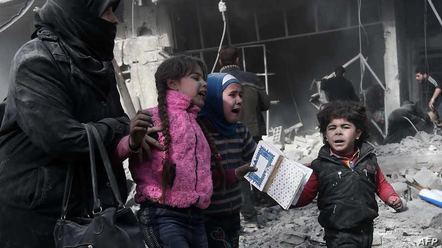 أم وأطفالها يحاولون الاحتماء من قصف النظام السوري على الغوطة الشرقية