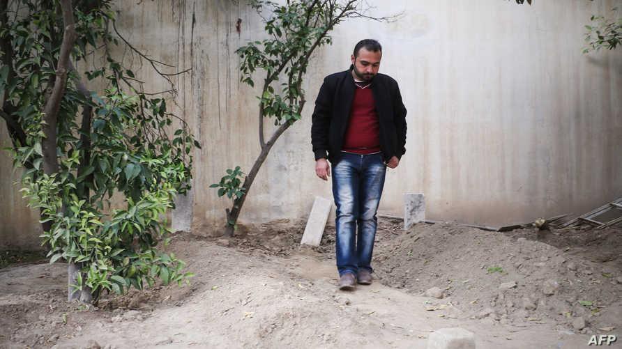 عراقي يقف أمام قبر أحد أفراد عائلته