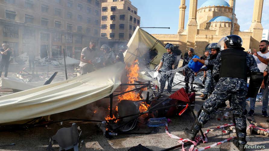 """رجال شرطة لبنانيون يحاولون إخماد النيران التي أشعلها مناصرون لـ""""حزب الله"""" بخيم المتظاهرين ضد الحكومة اللبنانية"""