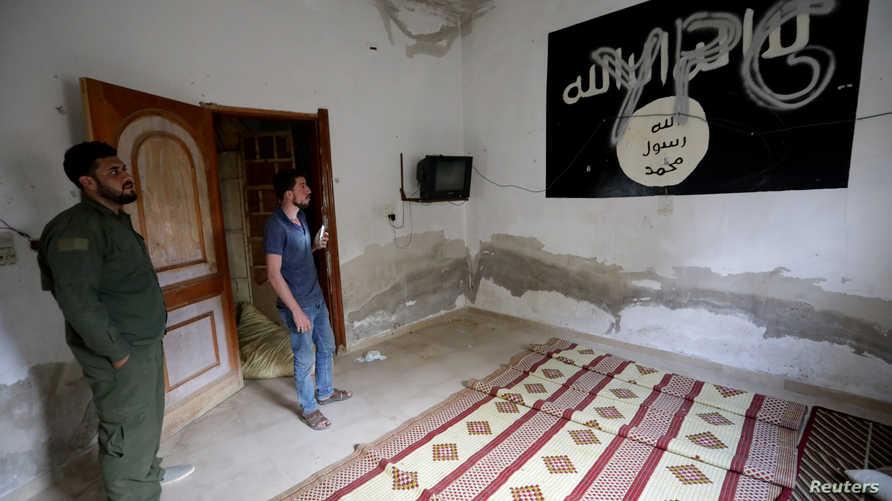 """الحروف الأولى لـ""""قوات حماية الشعب الكردية"""" مكتوبة على جدارية لعلم داعش داخل منزل في مدينة تل أبيض، شمالي سوريا"""