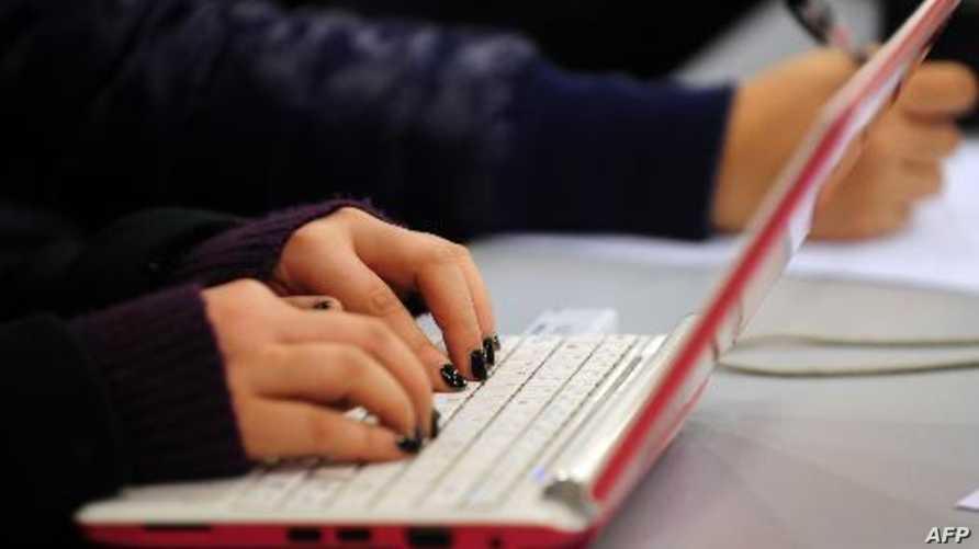 امرأة تستخدم كمبيوترا محمولا