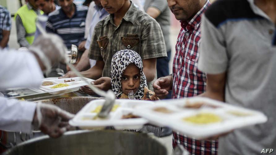 طفلة سورية لاجئة تنتظر في الطابور للحصول على وجبة غذاء