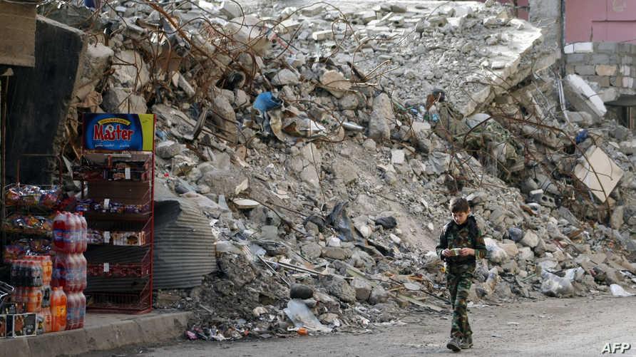 فتى يمشي في شارع مدمر في دير الزور