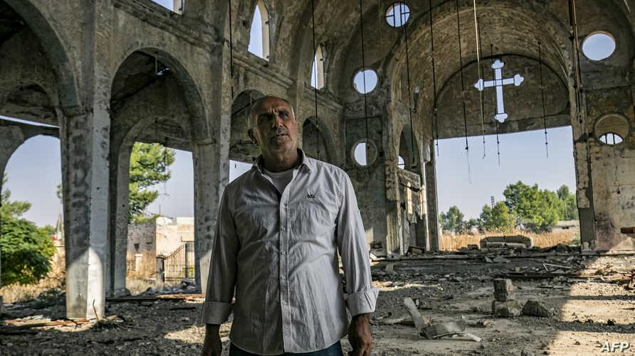 سركون صليو (50 عاماً) داخل كنيسة قريته تل نصري التي دمرها التنظيم المتطرف عام 2015 خلال هجومه على المنطقة