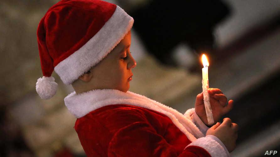 طفل أثناء مراسيم الاحتفال بعيد الميلاد في كنيسة مار يوحنا