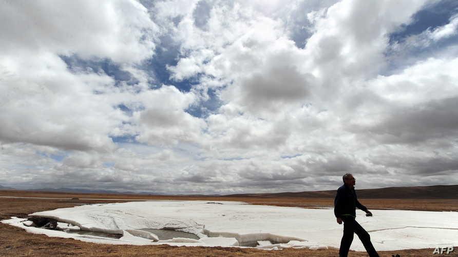 رجل يسير في منطقة جليدة سابقا، ذابت بسبب التغير المناخي، وكانت تعد من مصادر المياه للنهر الأصفر في الصين