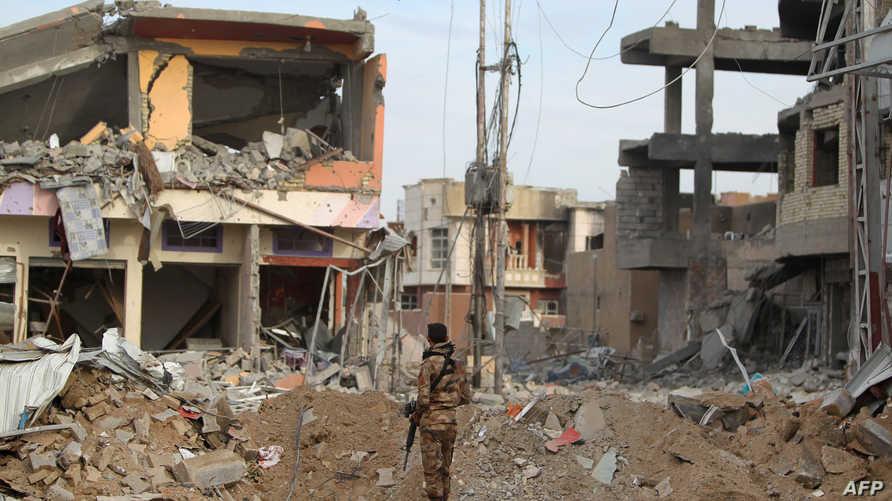 عنصر تابع للقوات العراقية يشاهد الخراب الذي خلفته المعارك ضد داعش