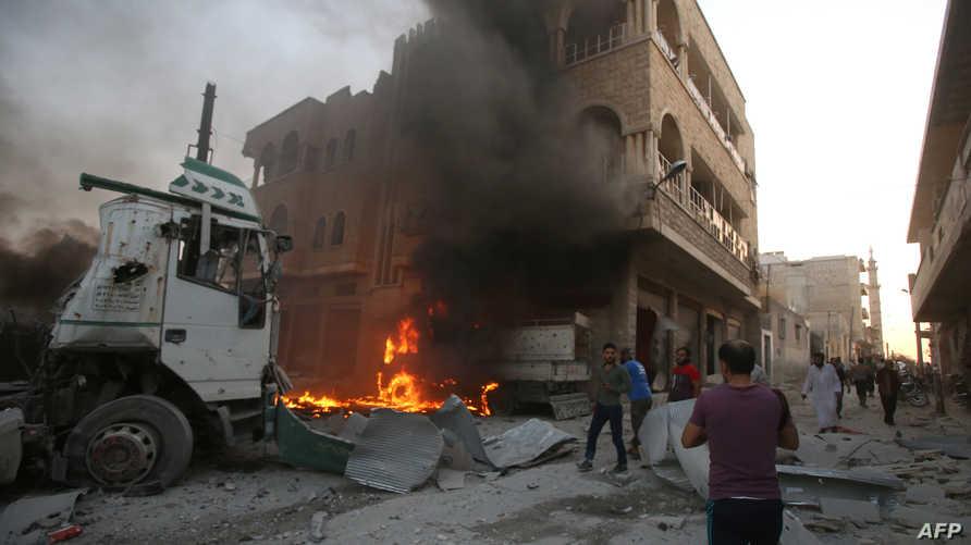 مدنيون يسيرون بين الركام إثر غارة في معرة النعمان بمحافظة إدلب
