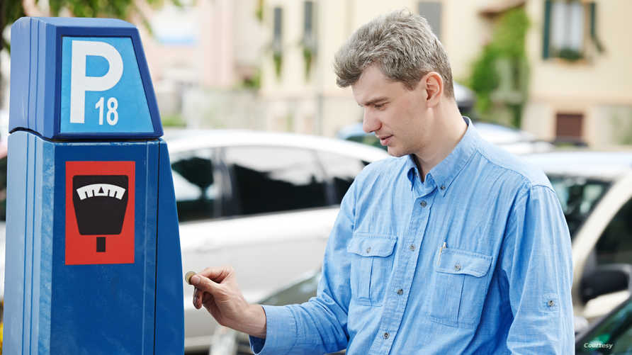 سائق يدفع مبلغا ماليا في موقف للسيارات