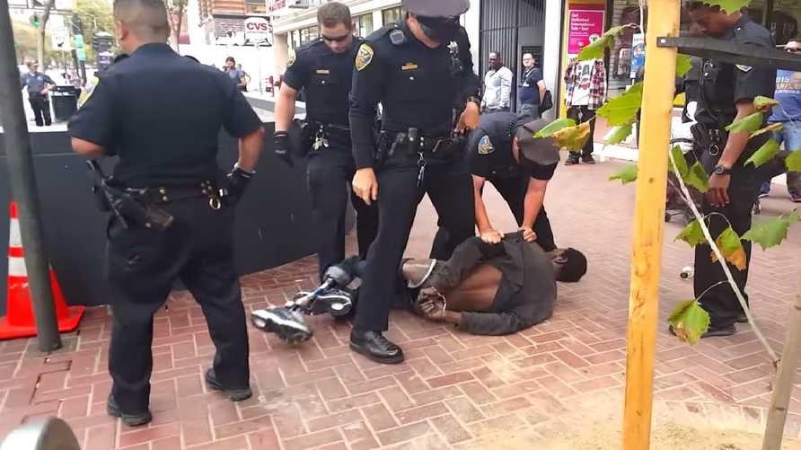 لقطة من الفيديو تظهر الشرطة تمسك بالرجل وهو بقدم واحدة