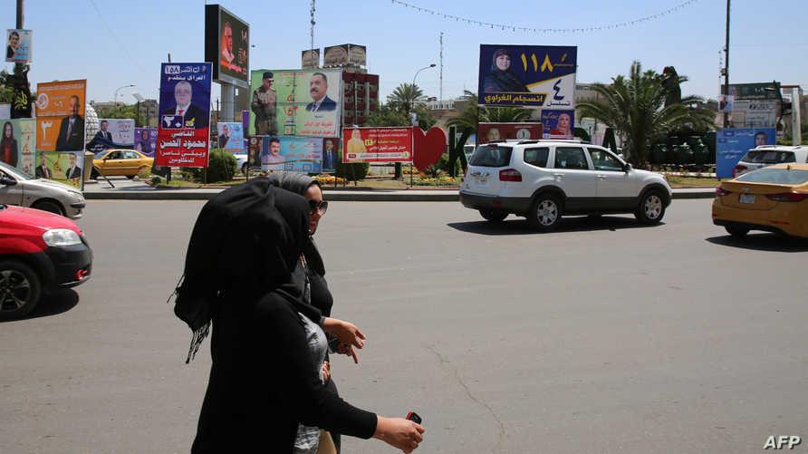 عراقيتان تسيران قرب لافتات لمرشحين للانتخابات وسط بغداد