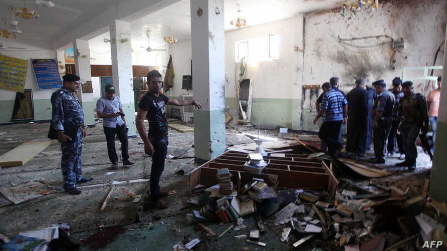 عراقيون يتفقدون آثار الدمار داخل حسينية الإمام علي بسوق الحدادين في منطقة بغداد الجديدة