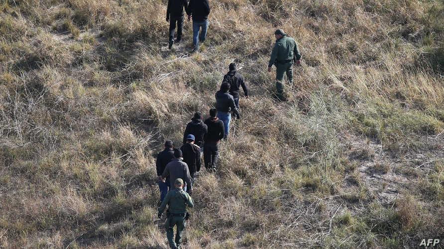 عناصر في حرس الحدود الأميركي يرافقون مهاجرين غير شرعيين قرب الحدود الأميركية-المكسيكية في الـ10 من الشهر الجاري