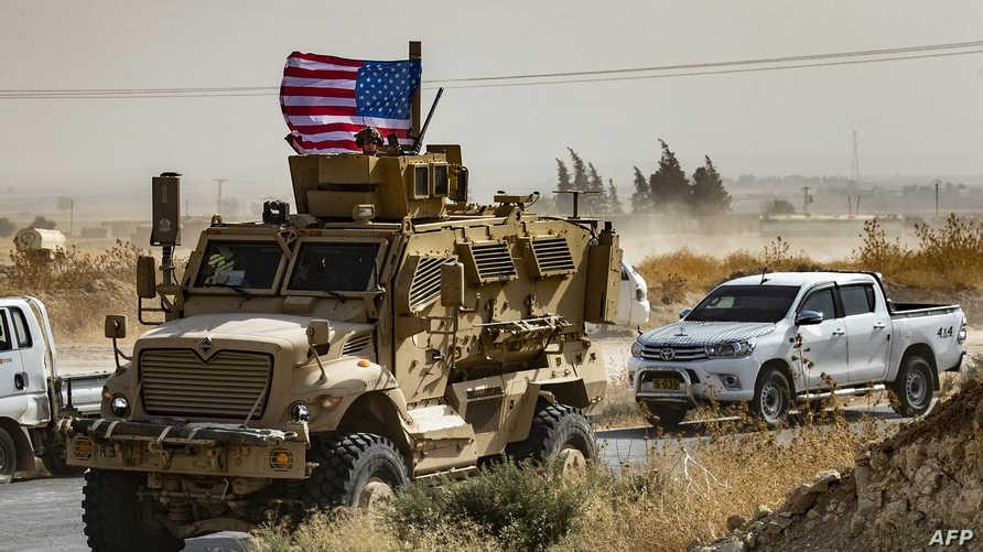 جندي أميركي فوق دبابة خلال مظاهرات للأكراد السوريين ضد التهديدات التركية قرب قاعدة عسكرية للتحالف الدولي الذي تقوده الولايات المتحدة في 6 أكتوبر 2019