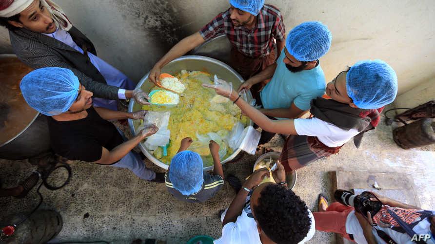 متطوعون يمنيون يعدون طعاما مجانيا خلال شهر رمضان