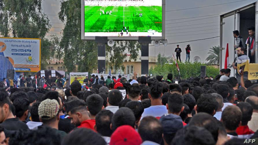 متظاهرون عراقيون يتابعون مباراة العراق وإيران في ساحة التحرير وسط بغداد