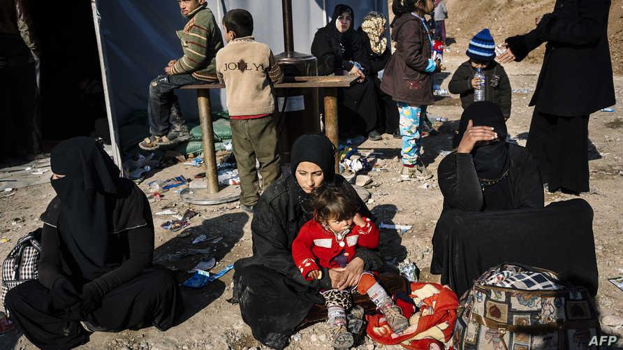 نازحون عراقيون فروا من الموصل بانتظار نقلهم إلى مخيمات قرب بلدة برطلة
