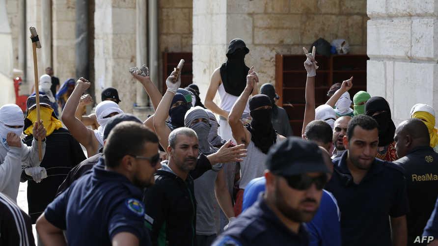 فلسطينيون ملثمون خلال مواجهات مع الشرطة الإسرائيلية في  مجمع المسجد الأقصى