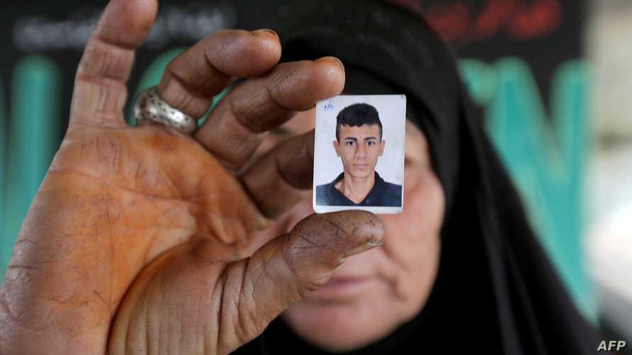 سيدة عراقية تحمل صورة ولدها بعد أن فقدت الاتصال به خلال الاحتجاجات في العراق
