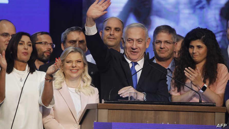 رئيس الوزراء الإسرائيلي بنيامين نتنياهو يلوح لمؤيديه وبجانبه زوجته في مقر الحملة الانتخابية