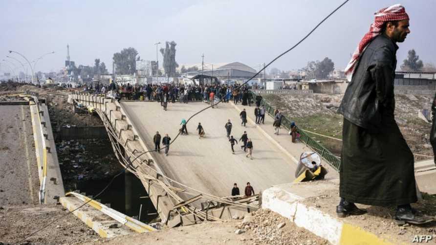 عراقيون يعبرون جسرا دمره داعش في الموصل