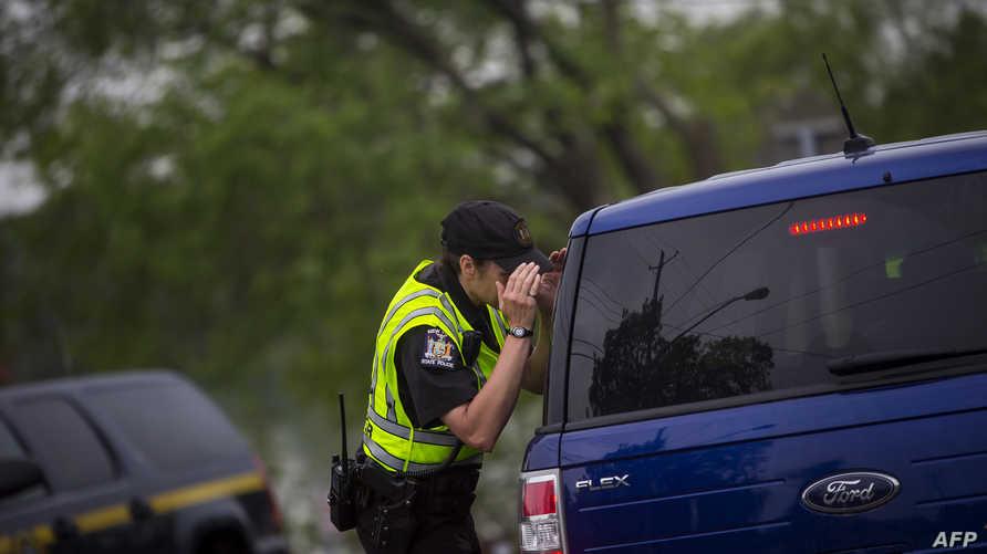 شرطي أميركي يتفقد سيارة خلال مطاردة أحد المشتبه فيهم- أرشيف