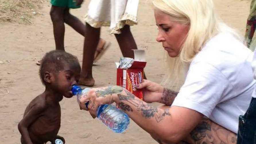عاملة الإغاثة تمنح الماء للطفل النيجيري المنبوذ