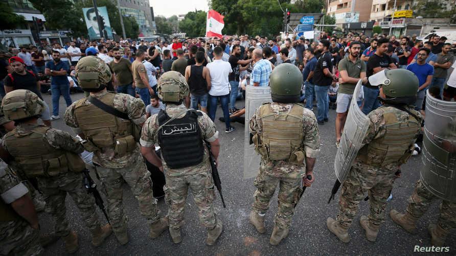 عناصر من الجيش اللبناني يقفون أمام متظاهرين في صيدا
