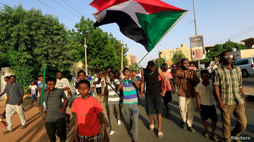 متظاهرون يلوحون بعلم السودان احتفالا بالتوصل لاتفاق بين المجلس العسكري وقوى المعارضة حول تسلم السلطة في 5 يوليو 209