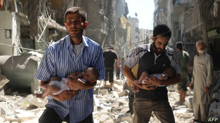 رجلان يحملان رضيعين عقب غارة للنظام السوري في مدينة حلب في 2016