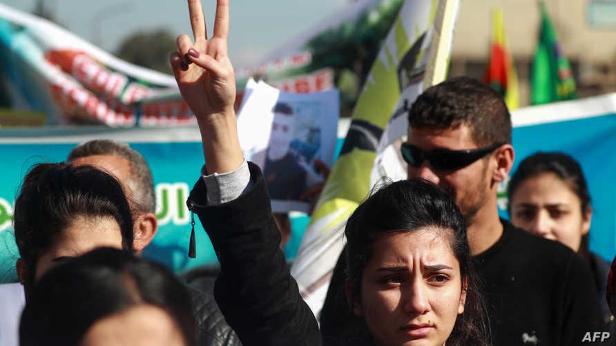 سيدة كردية ترفع شارة النصر خلال تظاهرة في مدينة القامشلي السورية