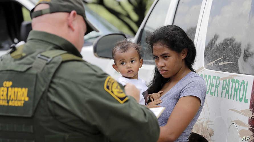 أم من هندوراس مع طفلها البالغ عاما بعد تسليم نفسها لحرس الحدود الأميركي إثر تسللها إلى ولاية تكساس