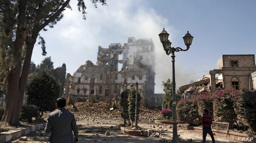 مسلحان من الحوثيين يتفقدان آثار غارة جوية نفذت على أحد المواقع بصنعاء