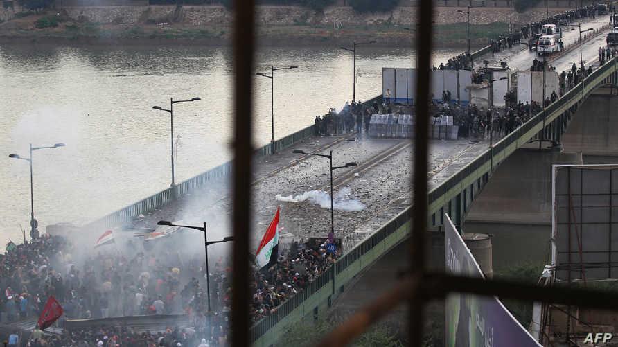 متاظهرون عراقيون يواجهون قمع الشرطة العراقية على جسر الجمهورية - 25 أكتوبر 2019