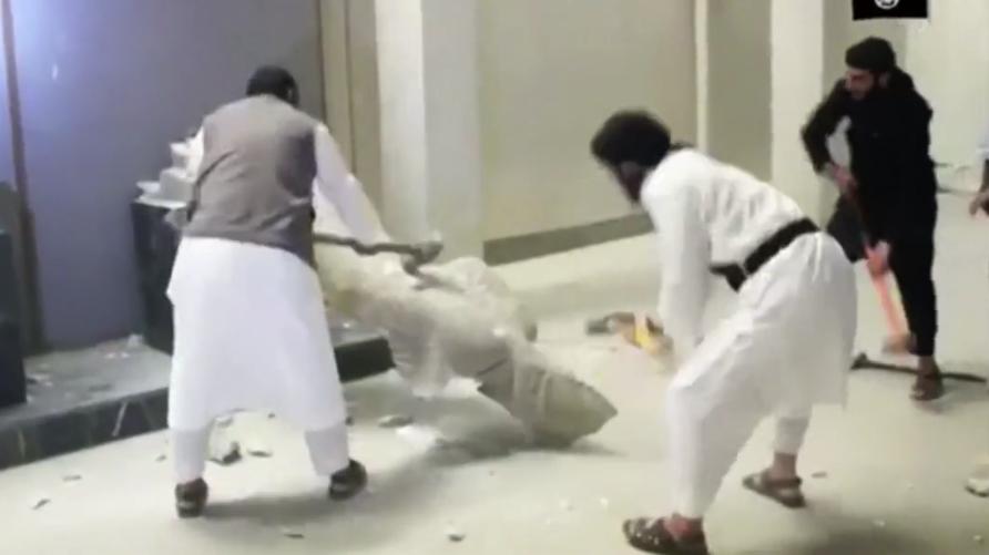عناصر من داعش تدمر القطع الأثرية في متحف الموصل (أرشيف)