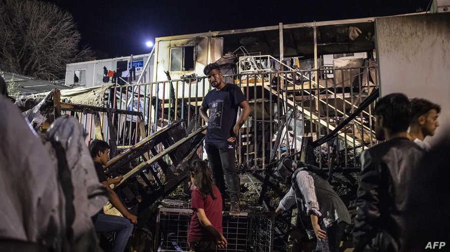 مهاجرون أمام الحاويات التي تعرضت للاحتراق في مخيم في جزيرة ليسبوس