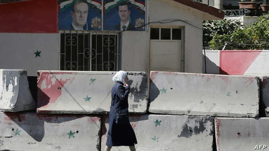 سيدة تسير بجانب حواجز إسمنتية في دمشق