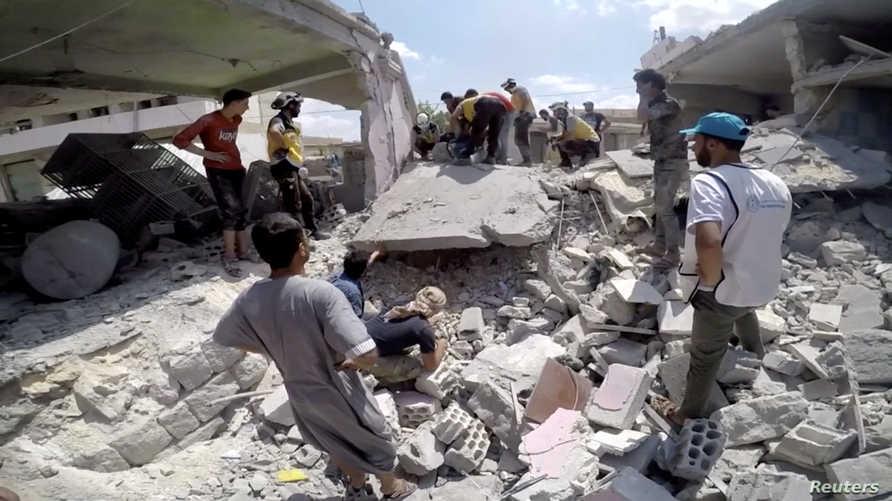 عمال إنقاذ من الخوذ البيضاء يبحثون بين ركام منازل مهدمة في محافظة إدلب
