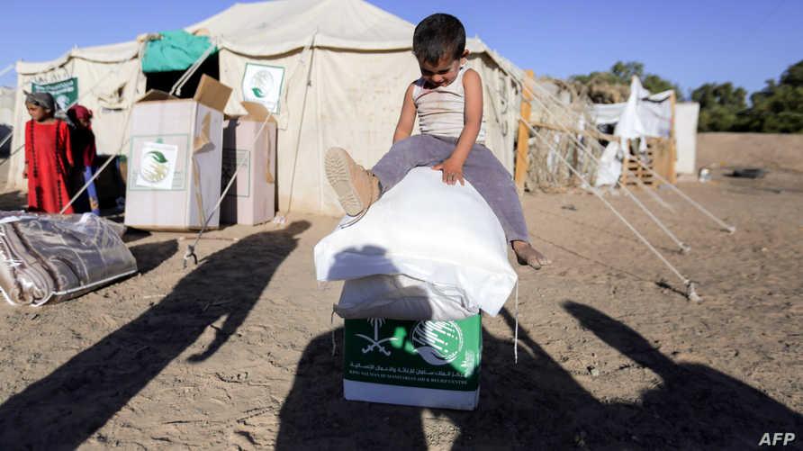 طفل يمني يجلس على صناديق مساعدات سعودية (أ ف ب)