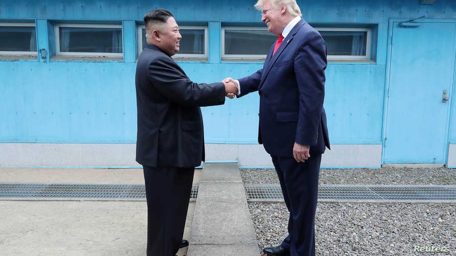 الرئيس الأميركي دونالد ترامب يصافح الزعيم الكوري الشمالي كيم جونغ أون عبر الحدود الفاصلة بين الكوريتين