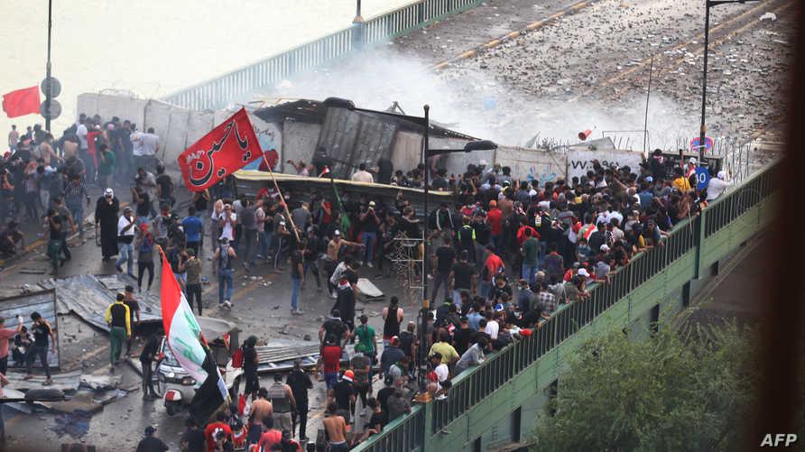 محتجون عراقيون يحاولون عبور جسر يربط ساحة التحرير بالمنطقة الخضراء وسط بغداد