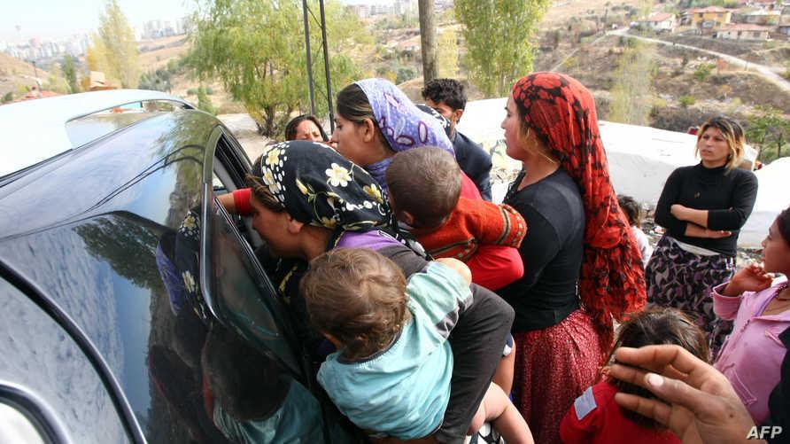 لاجئون سوريون يتلقون مساعدات غذائية في خيم وسط تركيا