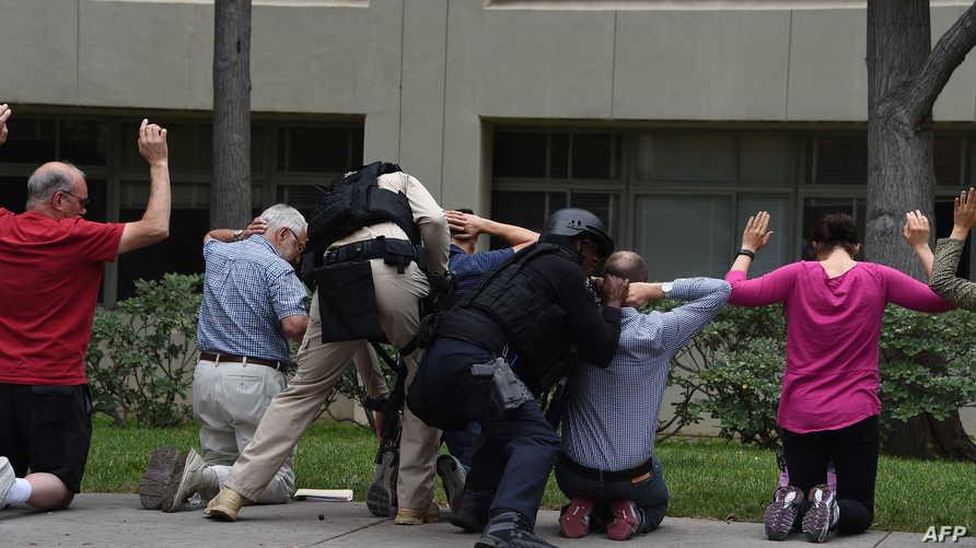 رجل أمن يجري تفتيشا للمواطنين في ساحة جامعة كاليفورنيا التي شهدت إطلاقا للنار الأربعاء